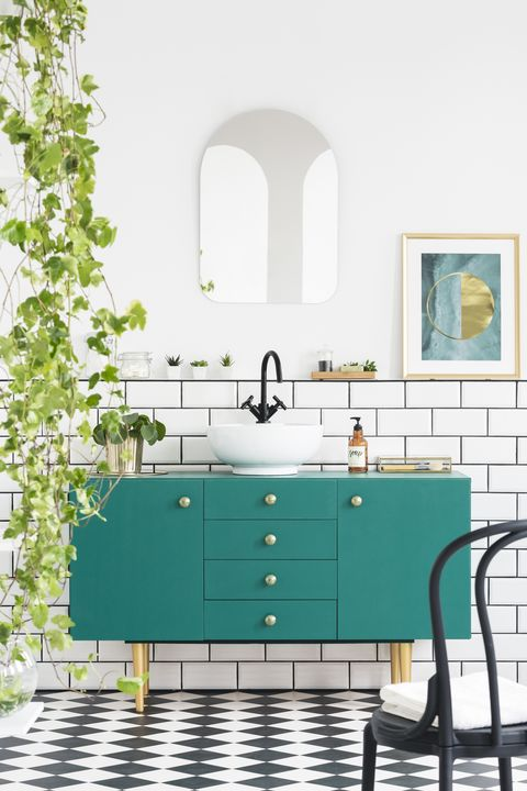 Mirror and poster above green cabinet in bathroom interior with black chair and plants. Real photo